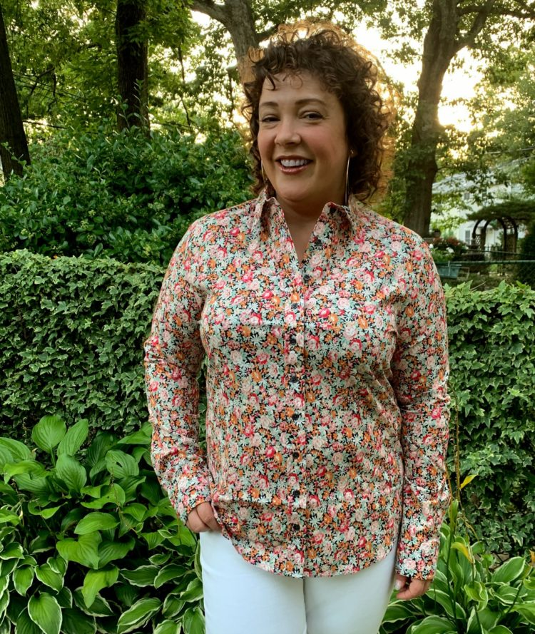 woman in pink and orange floral button front long sleeved shirt smiling at the camera with one hand in the front pocket of her white jeans