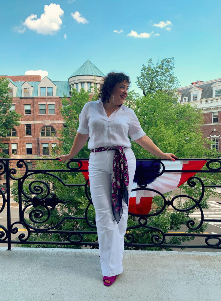 woman in white linen shirt tucked into white high rise wide leg denim trousers with a navy and magenta chiffon scarf tied around her waist as a belt. She is standing on a balcony overlooking Dupont Circle in DC and smiling.