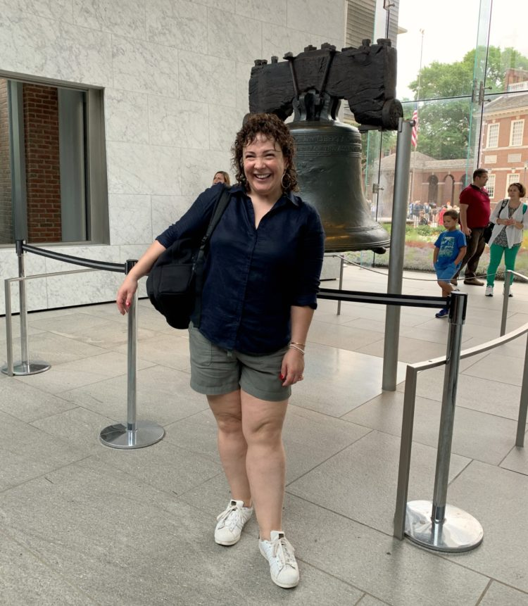 woman in navy linen shirt and olive chino shorts standing in front of the Liberty Bell