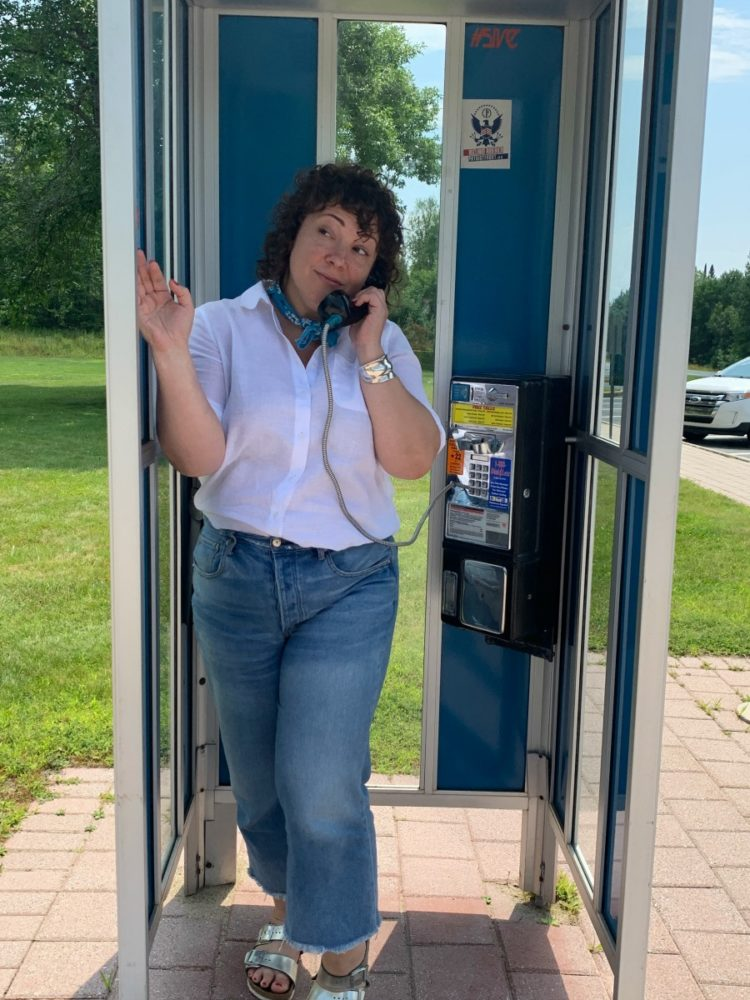 woman in white linen shirt and cropped jeans standing in a phone booth