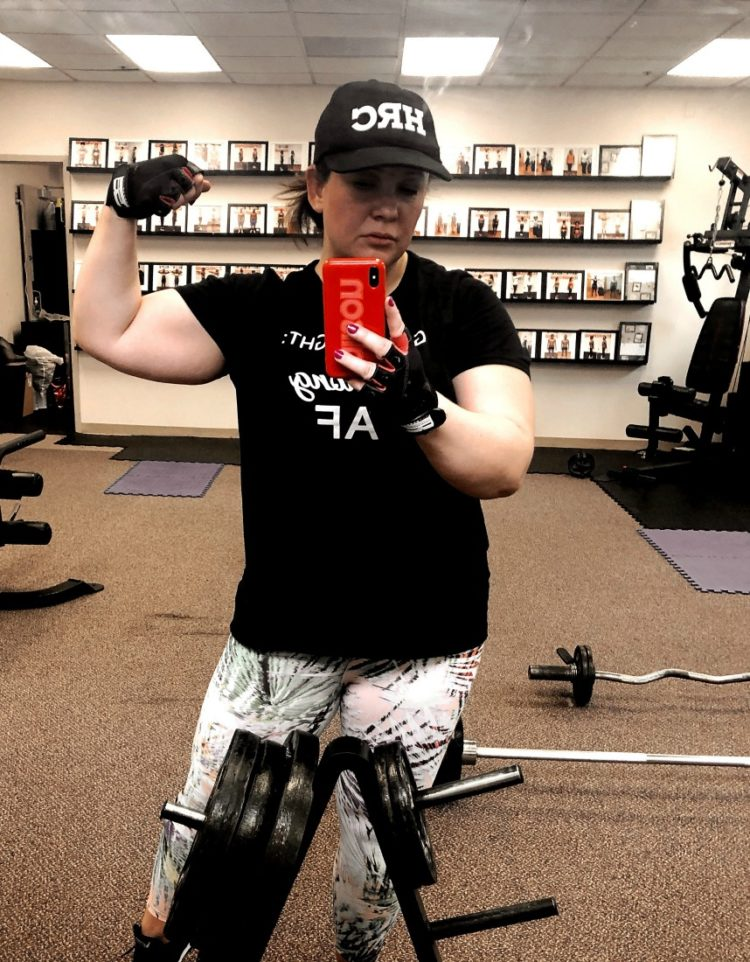 woman taking mirror selfie with one arm flexed to show her biceps