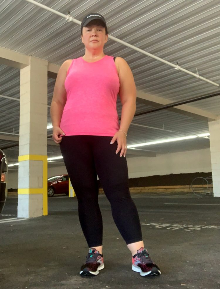 woman in pink activewear sleeveless top and black leggings standing and staring at the camera