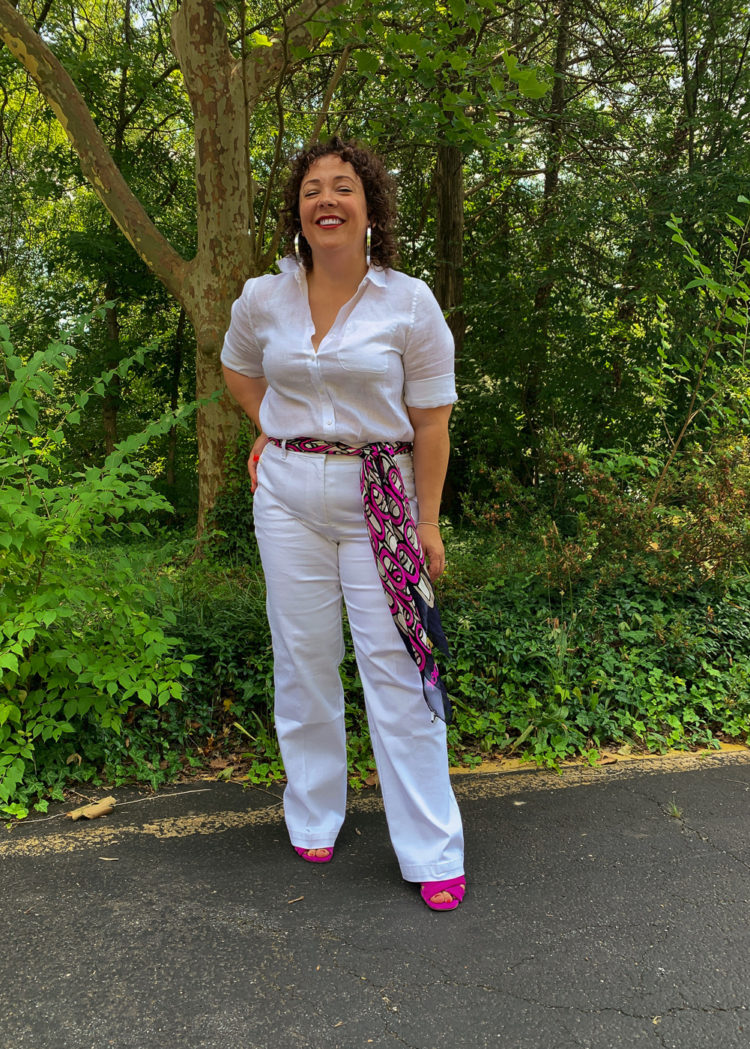 Woman in white linen shirt and white jeans with a colorful scarf tied as a belt smiling with hand on hip