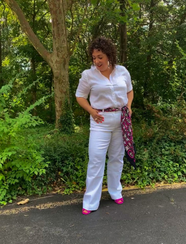 Woman in white linen shirt and white wide leg jeans standing in front of a forest looking down at her shoes.