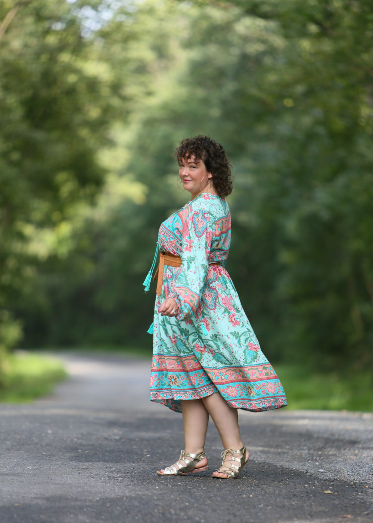 woman in green and pink floral dress walking away from the camera but looking back
