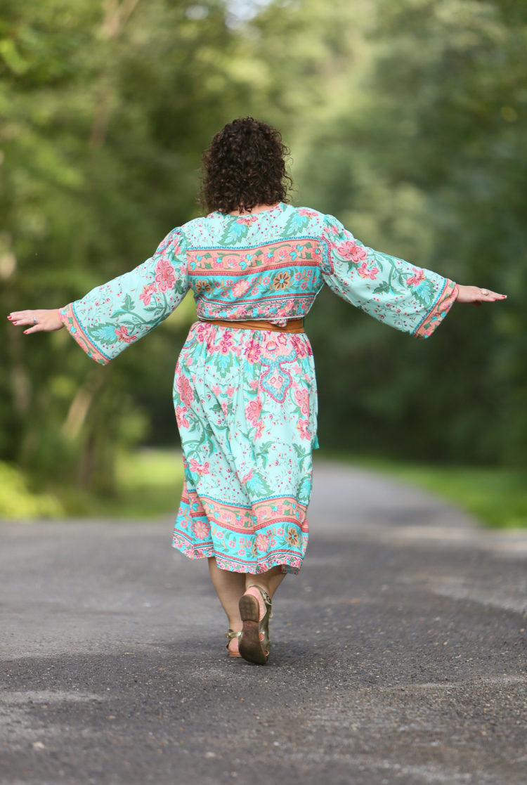back view of a woman in a light green floral boho inspired midi length dress
