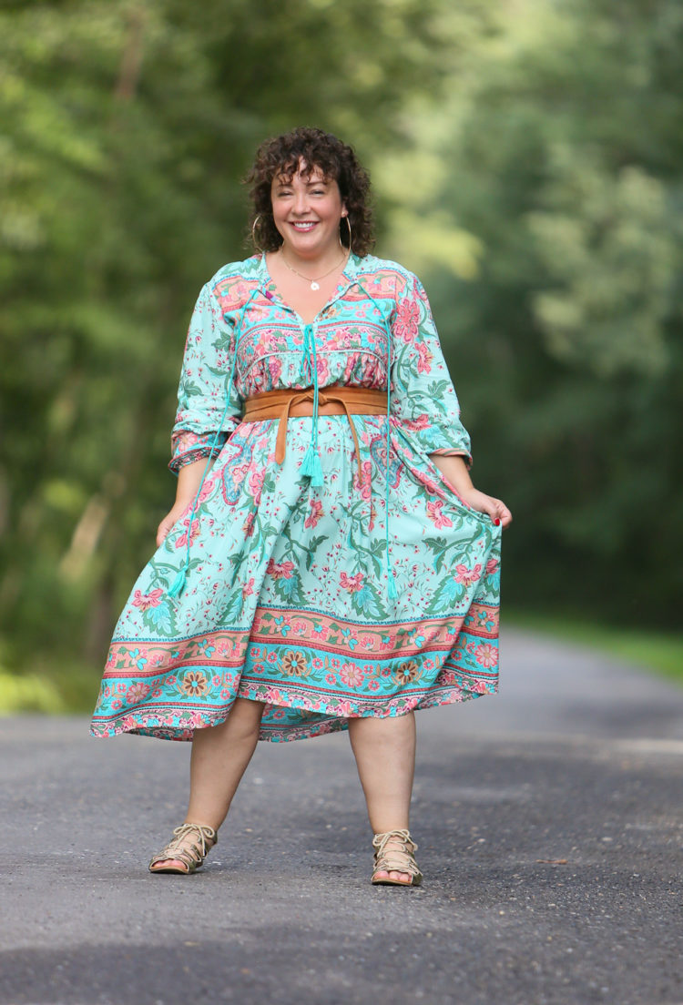 woman in a green floral dress cinched with a tan obi belt