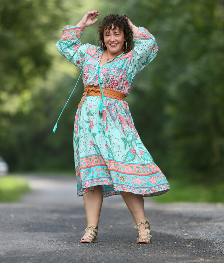 woman in light green floral dress cinched with a tan obi belt