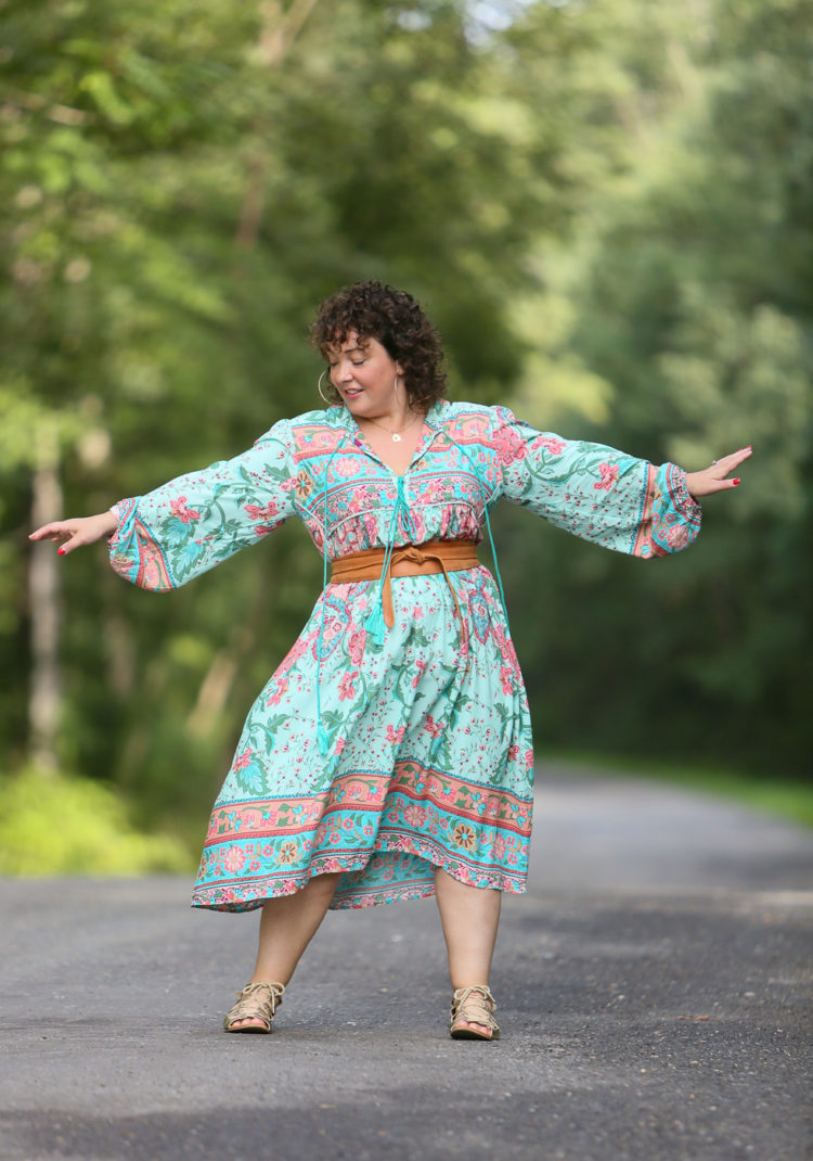 woman in a boho inspired dress with her arms out dancing