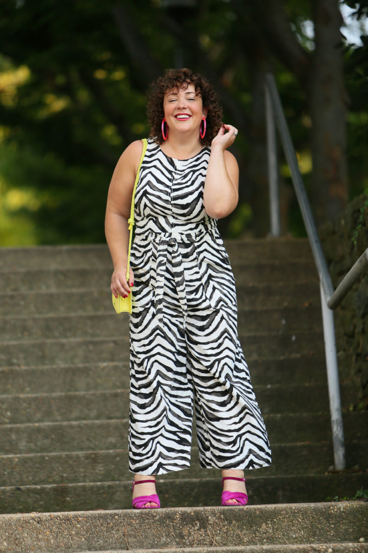 Wardrobe Oxygen in a zebra print jumpsuit from Banana Republic with a highlighter yellow Dagne Dover bag and hot pink heels and BaubleBar lucite hoops
