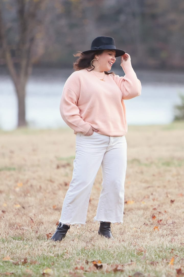 woman in peach sweater and white wide leg cropped jeans standing in a field tipping her hat