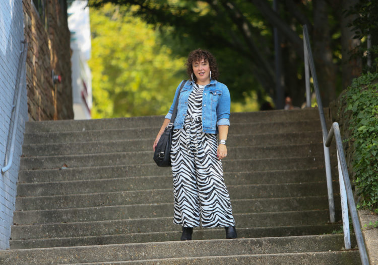 Styling a summer jumpsuit for fall - tips on how to do this successfully by Wardrobe Oxygen who is wearing a zebra print Banana Republic jumpsuit with a denim jacket and black ankle booties by Clark's and carrying a Rough & Tumble handbag in black leather.