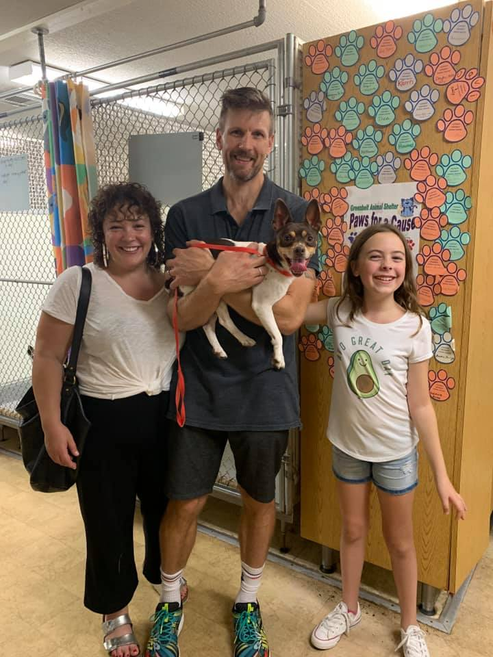 family holding a dog at an animal shelter