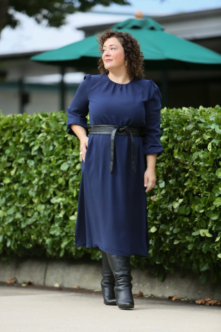 woman in a navy dress with a black leather obi belt and black heeled tall boots