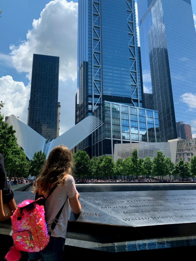 young girl looking into the 9/11 memorial fountain with the World Trade Center buildings and the Oculus in the distance.