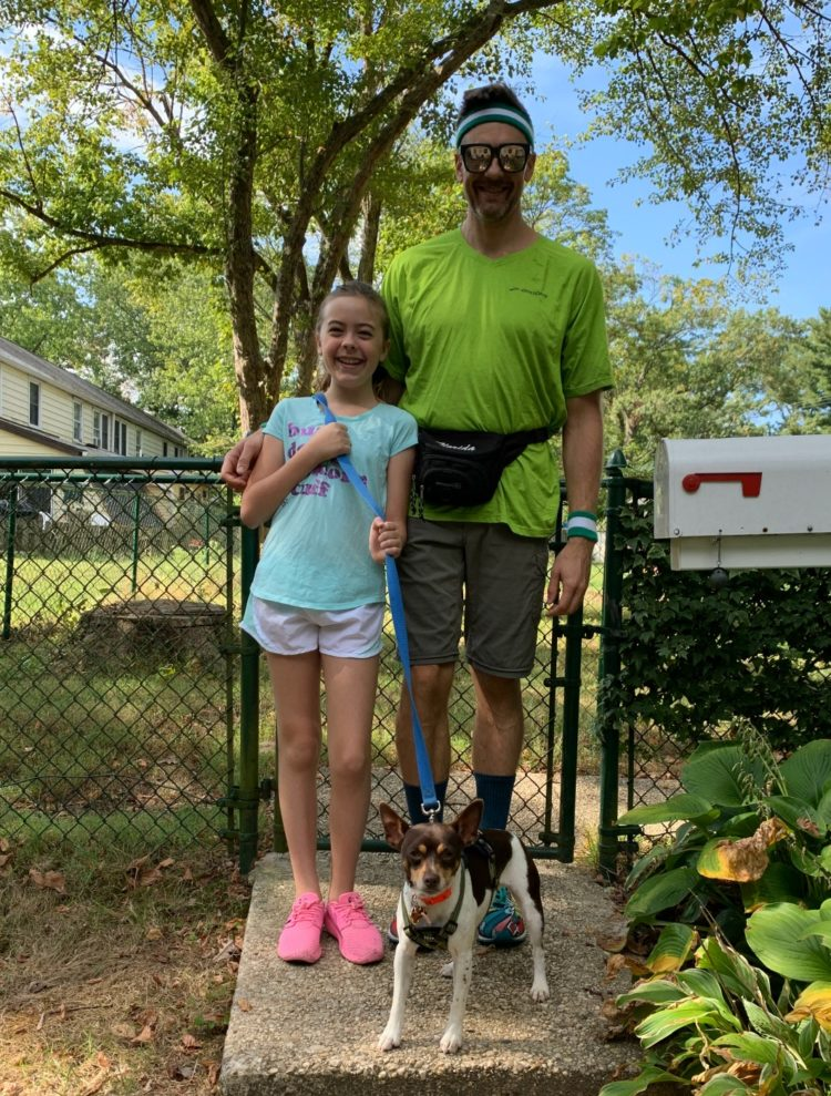 girl and her father dressed to go on a run with a dog on a leash