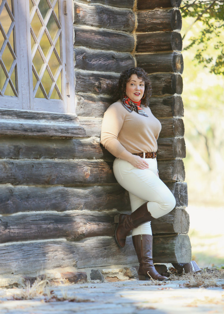 woman in cream jeans and a camel cashmere sweater leaning against a log cabin