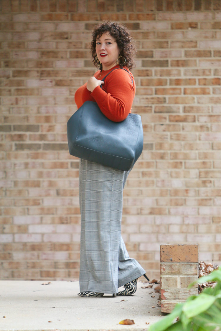 woman in an orange sweater and gray plaid pants carrying a teal blue leather tote walking out of an office building
