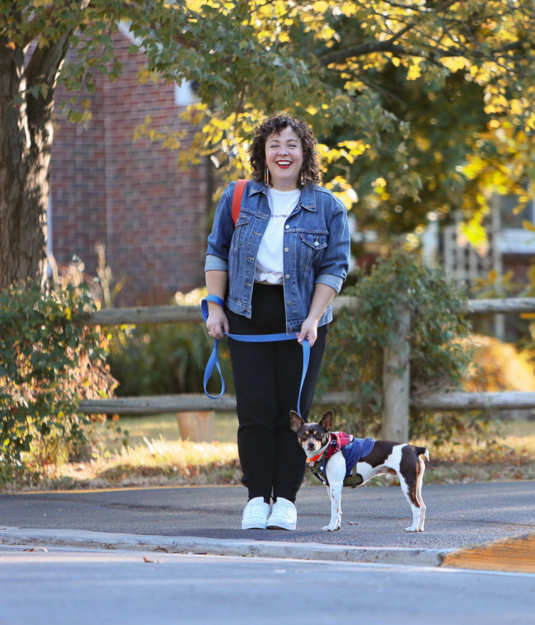 woman in a denim jacket and black knit joggers crossing the street while walking a dog