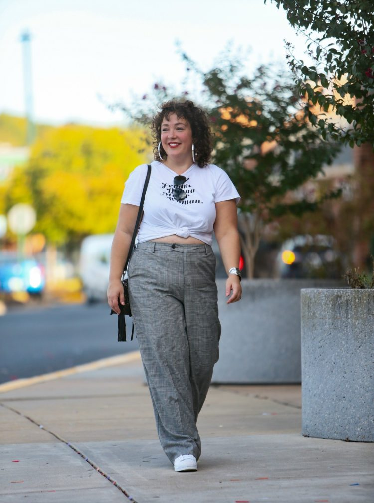 woman in wide leg gray pants and a white t-shirt knotted to show part of her stomach