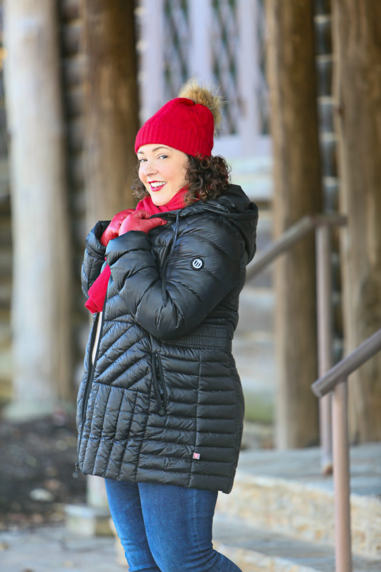 Woman in black puffer coat with red scarf and red hat looking at the camera