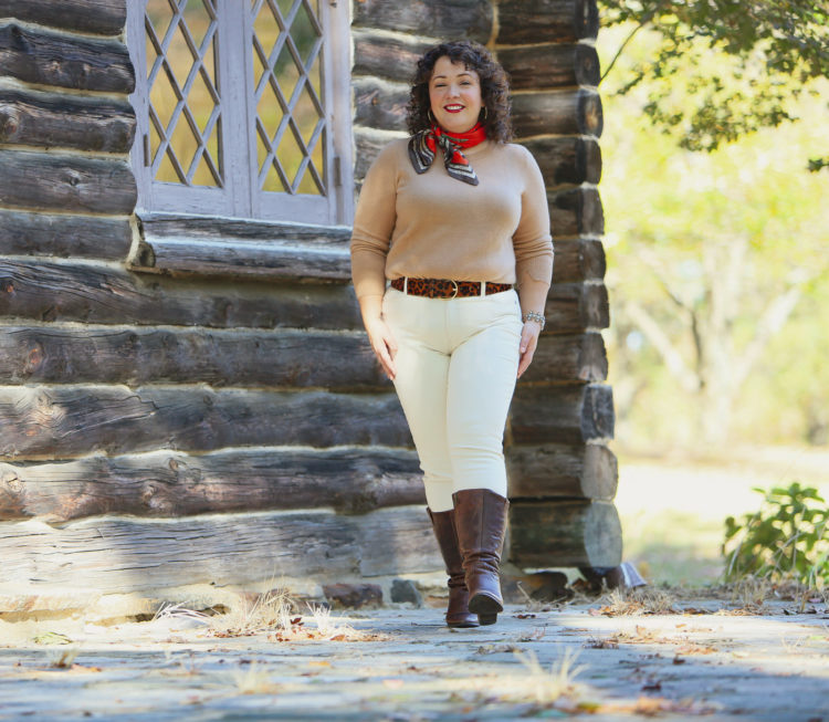 woman in a camel colored sweater, cream jeans, and brown knee-high boots walking towards the camera