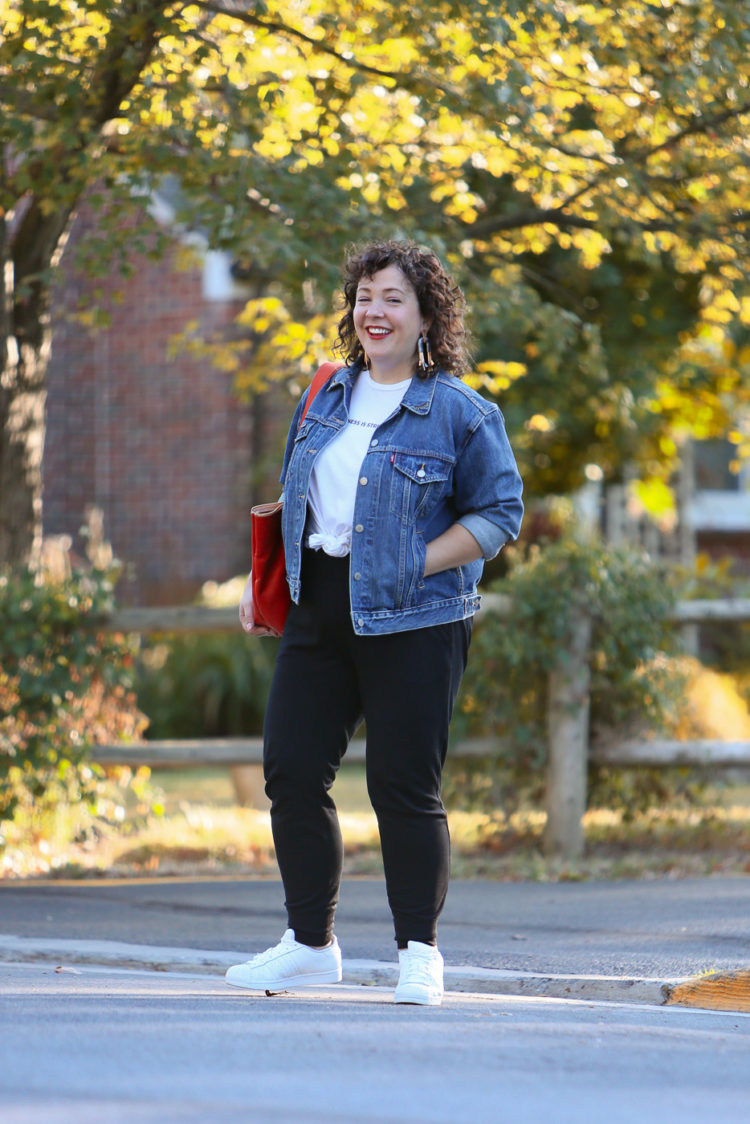 woman in a denim jacket and black knit joggers crossing the street