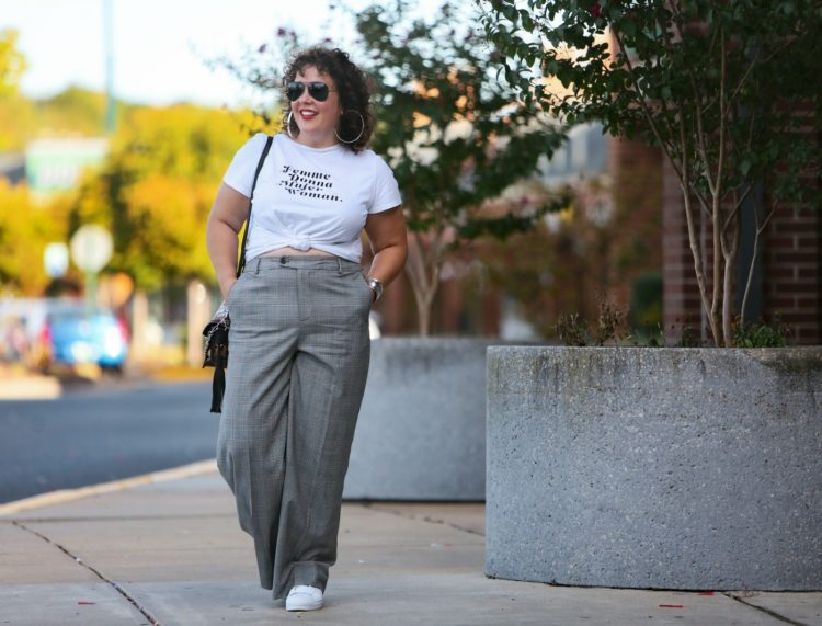 woman walking along a strip mall in white graphic t-shirt tied at her waist with gray glen plaid wide leg trousers