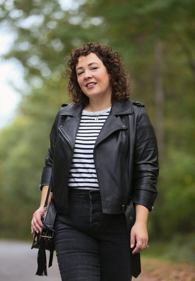 Alison in a black leather moto jacket, black and cream striped tee, gray jeans and white sneakers walking a small brown and white dog