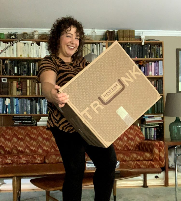 image of woman smiling while holding a large cardboard box that says Trunk Club on it