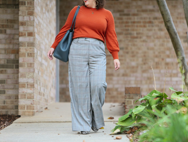woman in an orange long sleeved sweater tucked into gray plaid pants walking o a sidewalk looking to the side