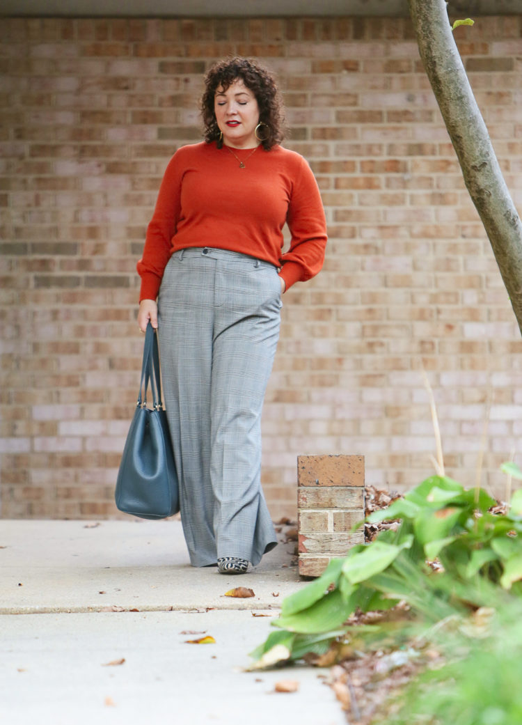woman in an orange sweater and plaid pants walking down a sidewalk