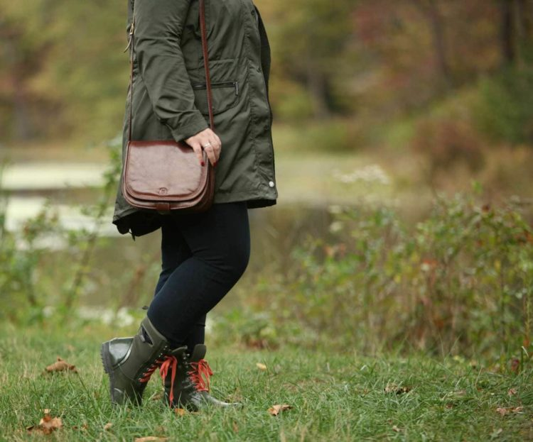woman in a raincoat and green lace-up rain boots