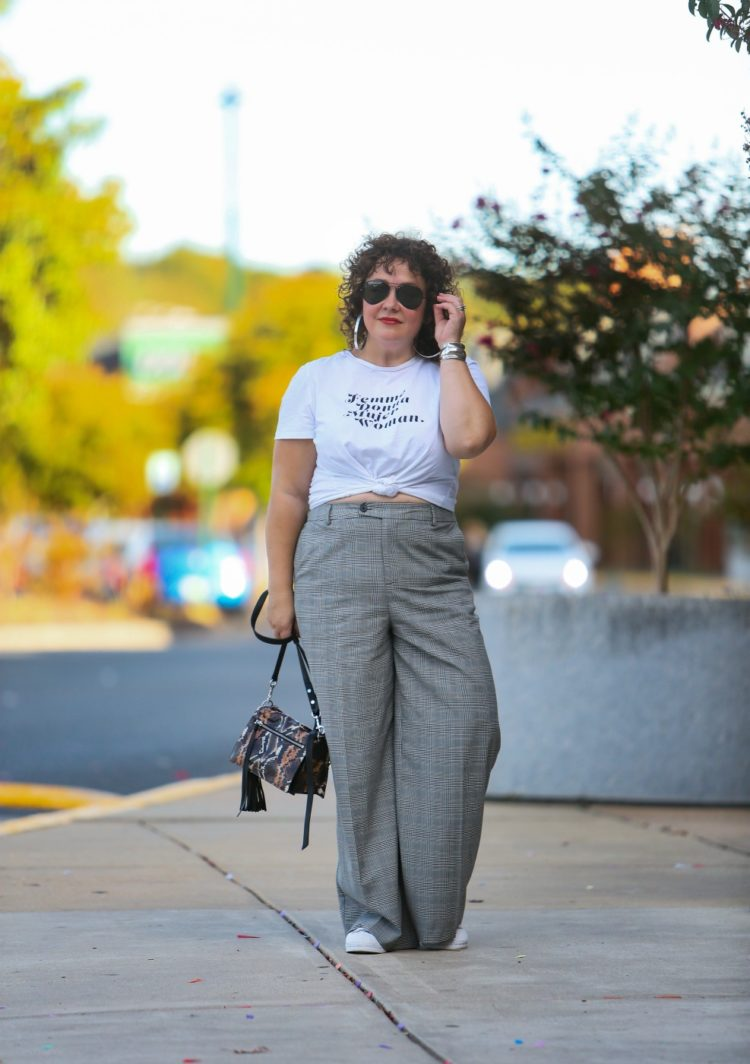 woman in wide leg gray pants and a white t-shirt knotted at her waist