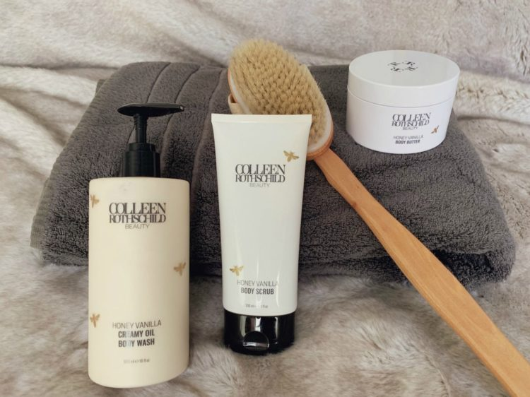 The Colleen Rothschild Beauty honey vanilla body care line displayed on a towel along with a dry brush