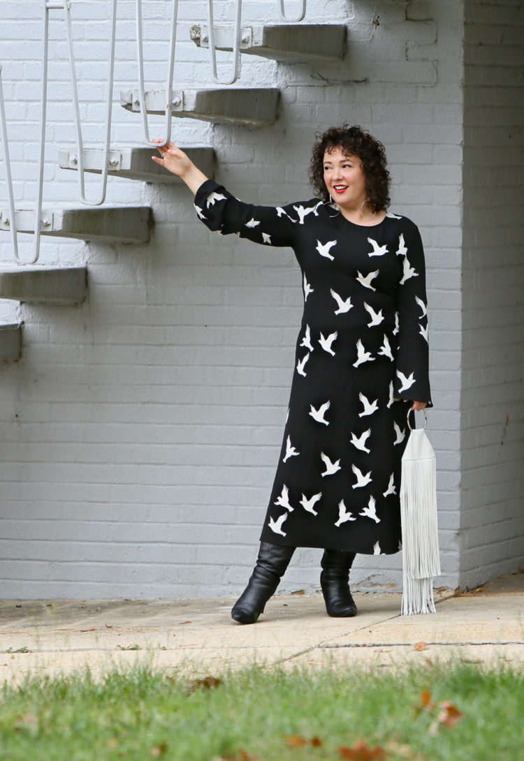 Black Stine Goya dress with white bird print styled with Kara Bags fringed purse and black heeled knee high boots