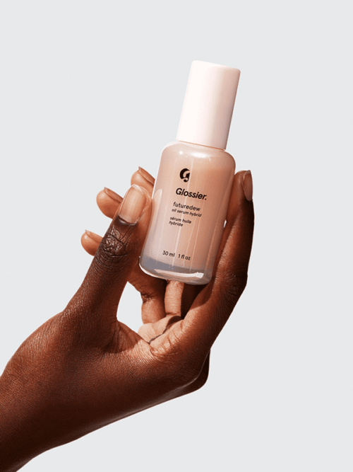 hand holding a bottle of Glossier Futuredew