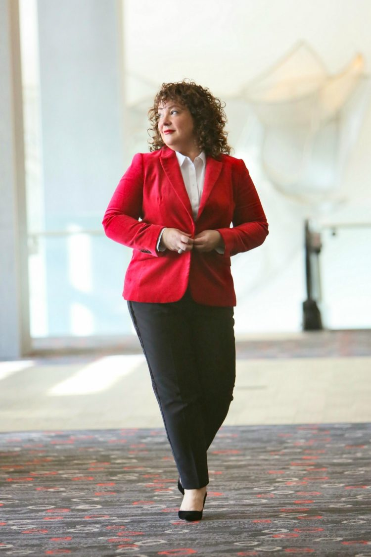 Alison buttoning her red velvet blazer