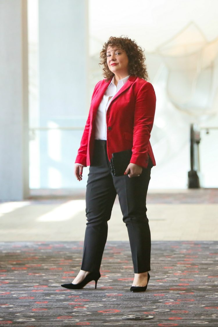 Alison in a red velvet blazer styled with a white button front shirt and black cigarette pants looking directly into the camera