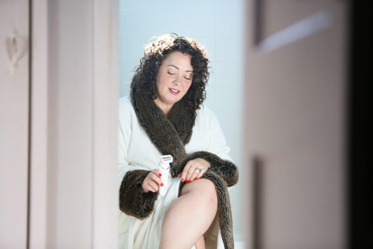 Woman in bathrobe sitting on the edge of a tub looking at an electric razor