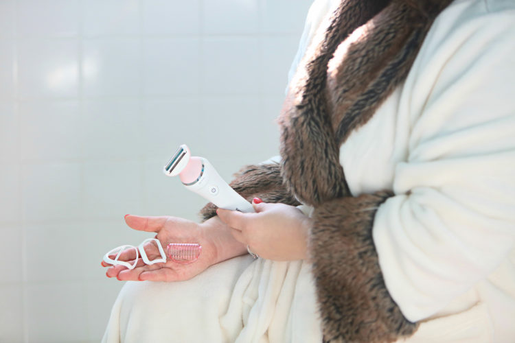 woman holding the Philips SatinShave electric razor and three attachments