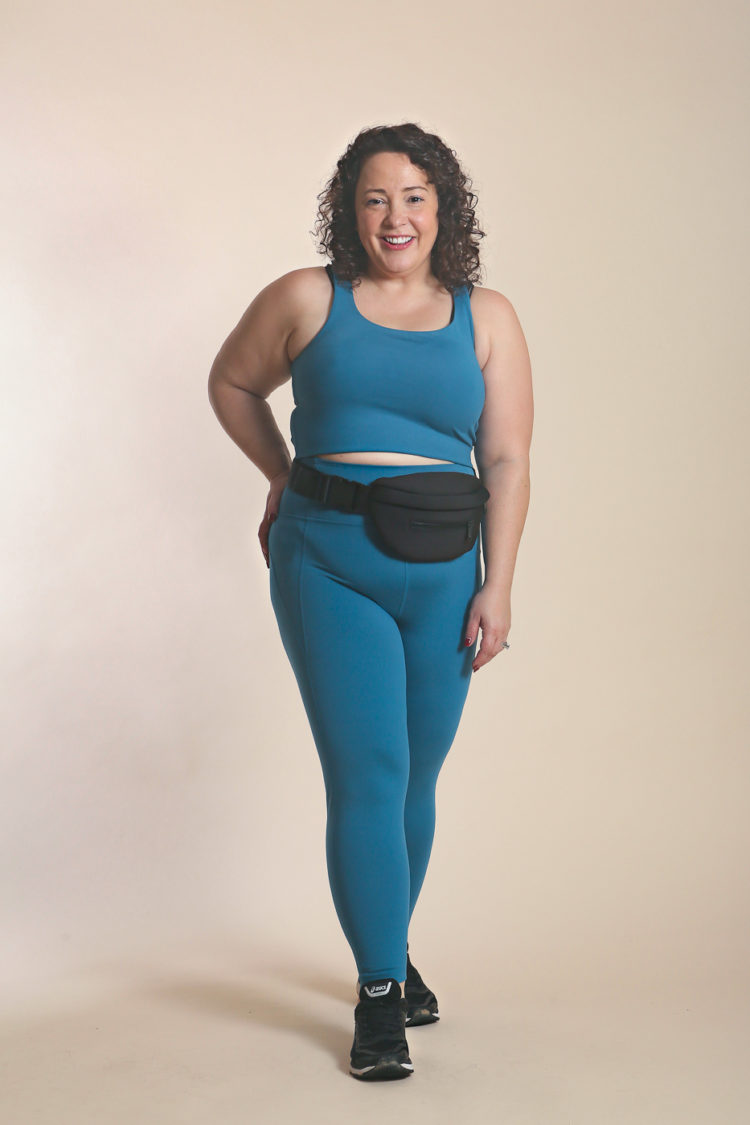 Woman in blue sports bra and leggings posing for the camera