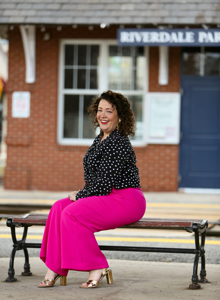 woman in pink pants and a black polka dot blouse sitting on a bench looking at the camera