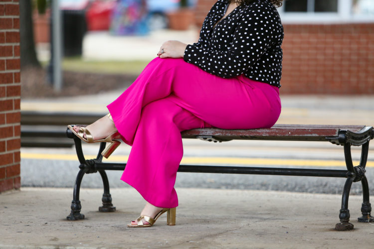 woman in pink pants and a black and white blouse with her legs crossed