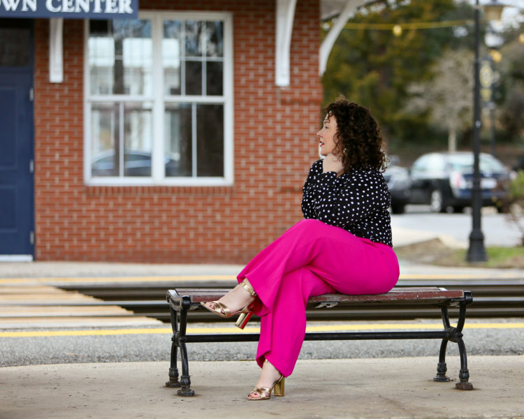 Woman in a polka dot blouse and hot pink pants with gold sandals sitting on a bench looking off into the distance