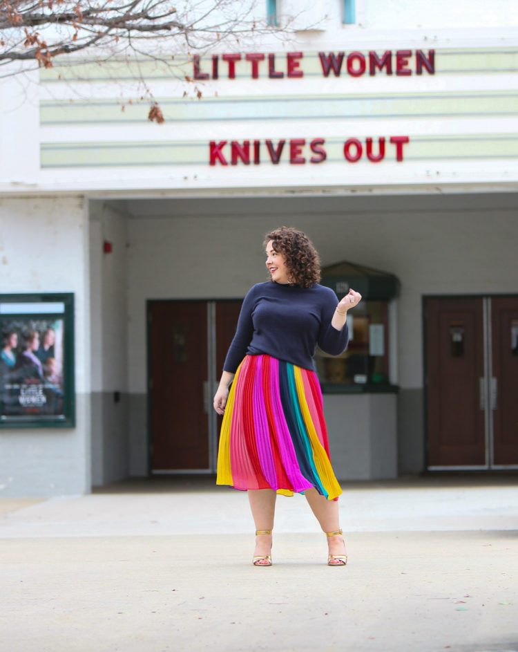 woman in a rainbow striped skirt and navy sweater standing in front of a movie theater