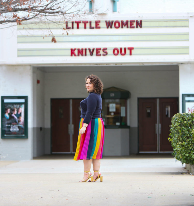 Woman wearing a rainbow stripe chiffon midi skirt and looking at the camera