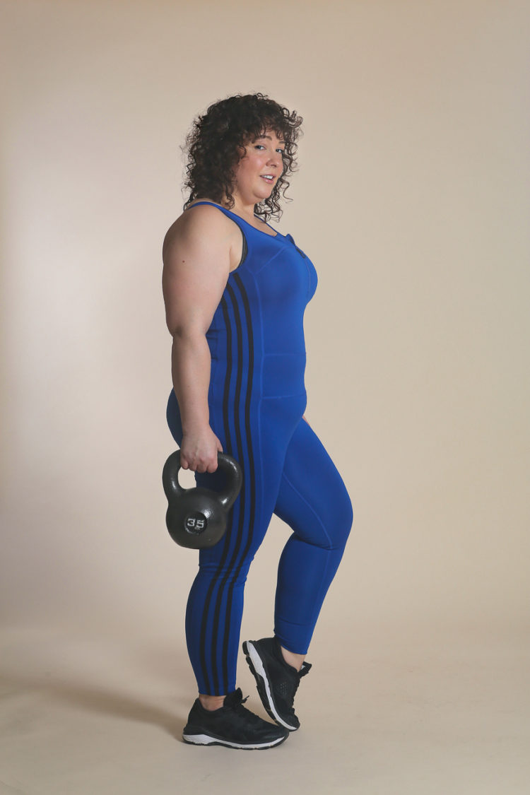 woman in blue bodysuit from adidas holding a kettlebell