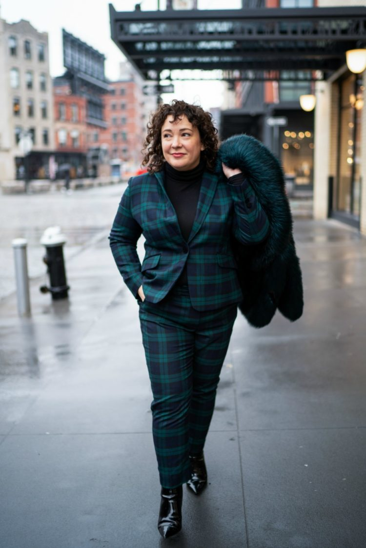 woman in a black watch plaid pantsuit carrying a dark green faux fur coat over her shoulder on the streets of New York City
