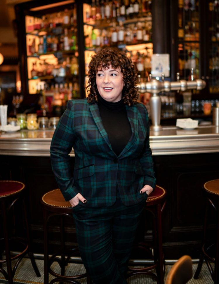 woman in a green plaid pantsuit standing in front of a bar at a French restaurant